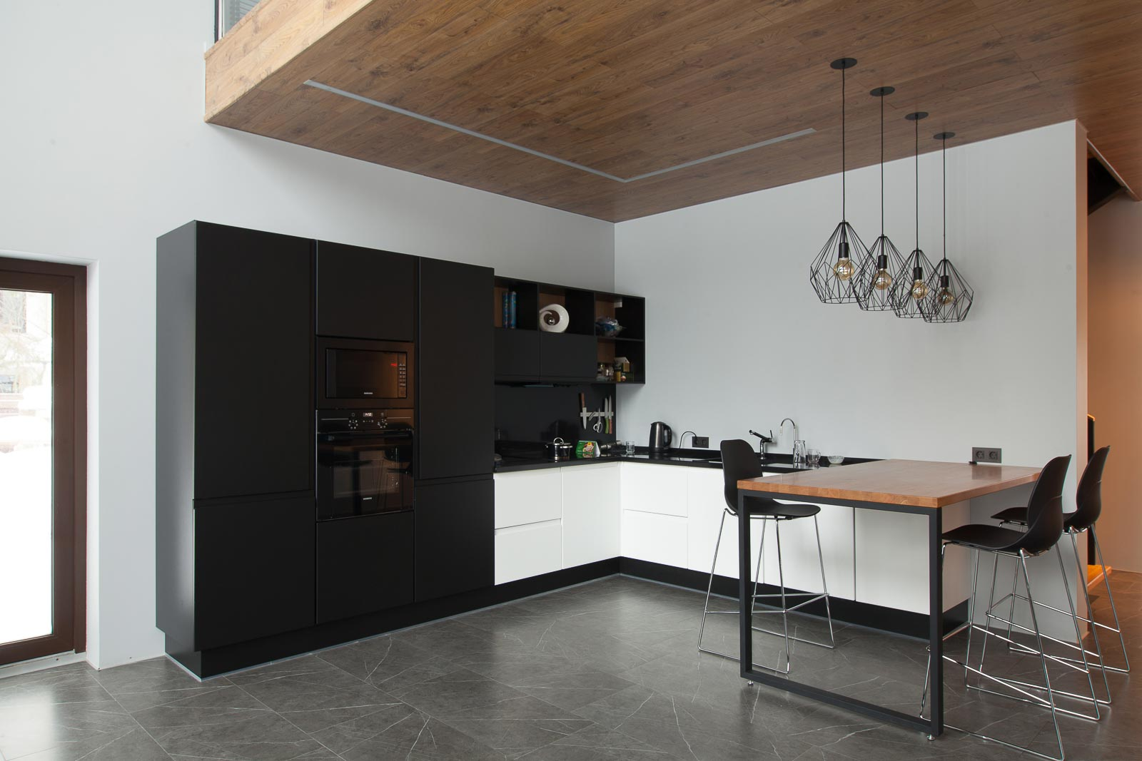 Black and white kitchen with wooden ceiling and floor with grey tiles