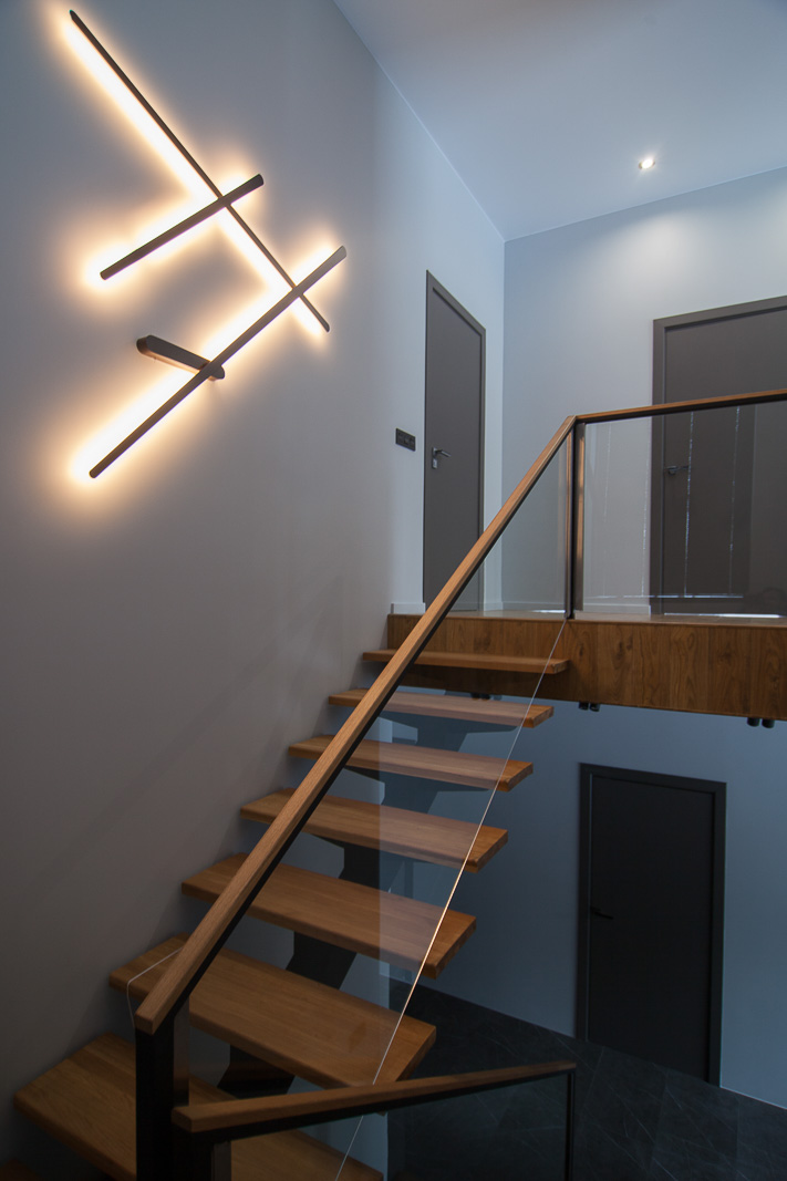 Staircase in wood and contemporary light on the wall