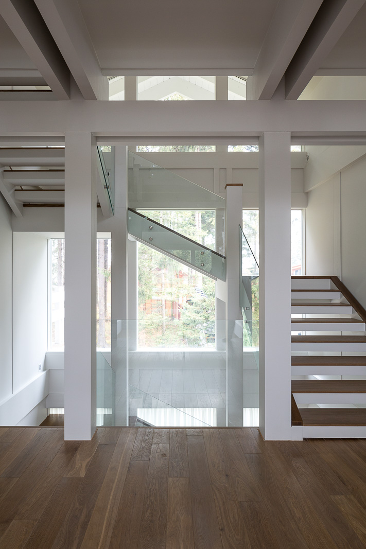 Stairs with glass rails in white inrterior in the half timbered house